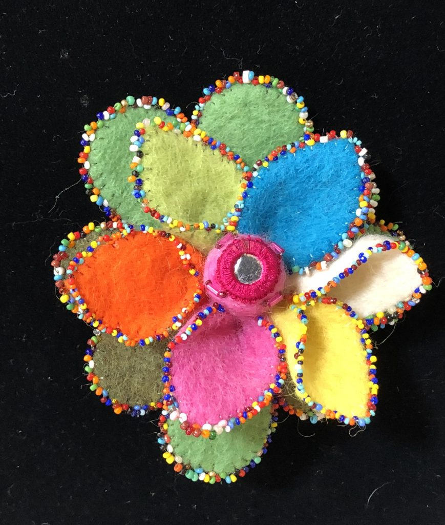 The felted flower is embellished with primary color beads in a random act of beading by Mary Ellen Beads Albuquerque.
